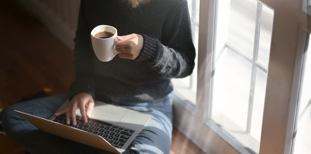 Person on computer holding a cup a coffee